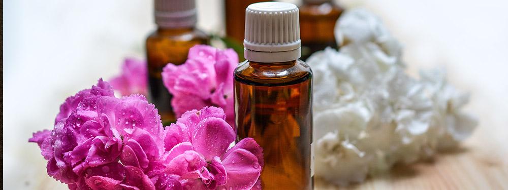 Photo de flacons d'huiles essentielles posés sur une table en bois avec des fleurs violettes et blanches