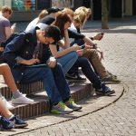 Photo de plusieurs jeunes assis sur un trottoir regardant leurs portables