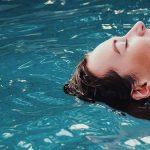Photo d'une femme heureuse allongée dans l'eau d'une piscine