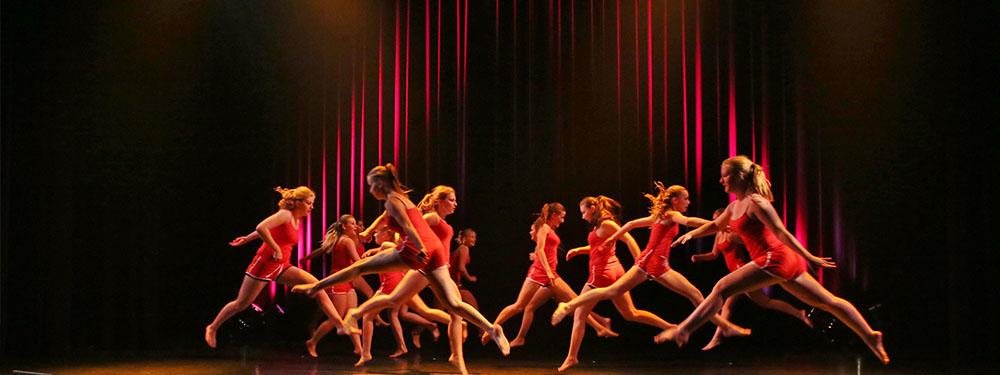 Photo d'un dizaine de jeunes danseuses sur scène en plein saut