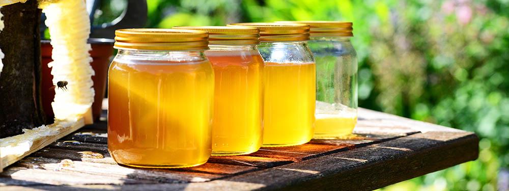 Photo de 4 pots de miel posés sur une table de jardin en bois
