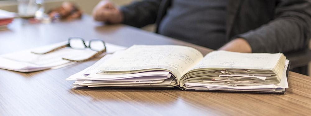 Photo d'un homme assis à une table devant un agenda bien remplis posé sur une table
