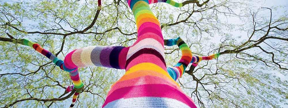 Photo d'un arbre habillé sur le tronc et les branches d'un pull en laine multicolor