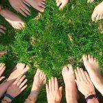 Cercle de mains de jeunes posées dans l'herbe