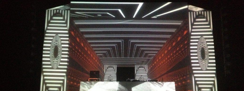 Photo représentant une projection lumineuse blanche et rouge sur une façade