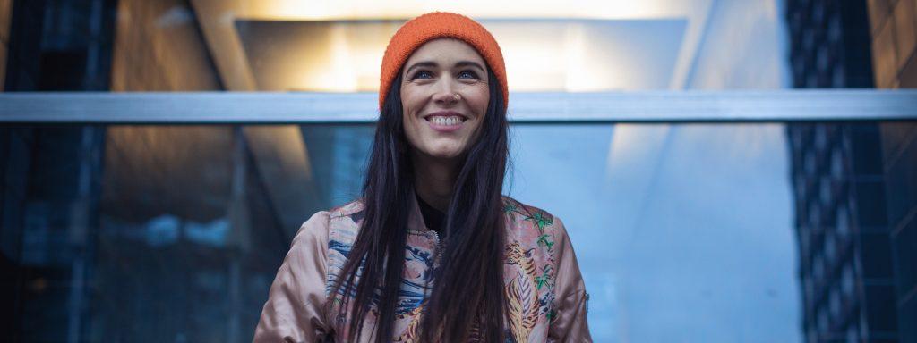 Photo représentant une jeune femme avec un bonnet orange devant une façade vitrée