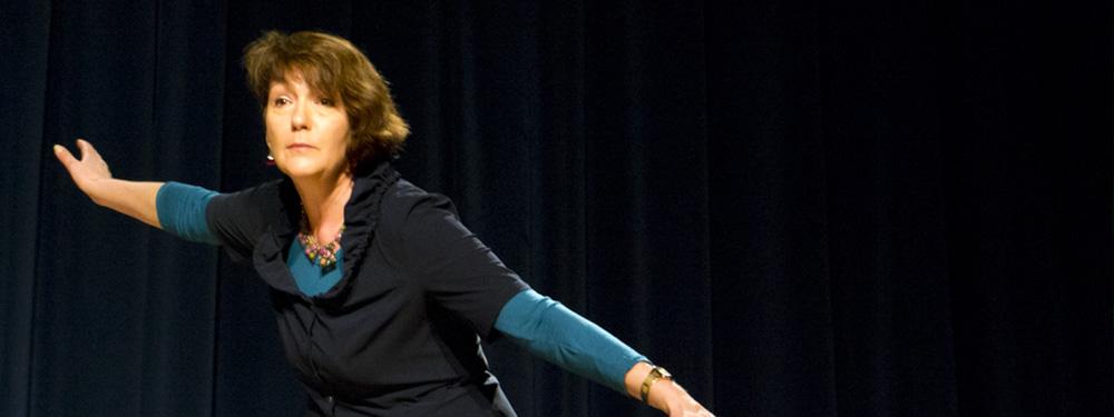 Photo de Marie Ricard les bras ouverts sur une scène