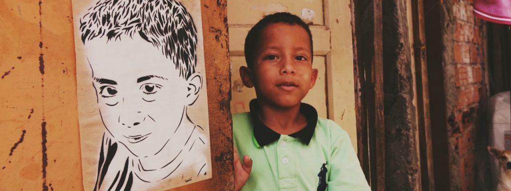 Photo représentant un petit garçon dans une rue, qui pose à côté de son portrait dessiné, collé sur le mur