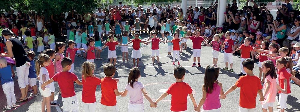 Photo de la fête de fin d'année dans l'une des écoles venelloises. Les enfants présentant leur spectacle en ronde devant leur parents ravis