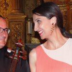Photo représentant un violoncelliste et une pianiste souriant devant un autel d'église