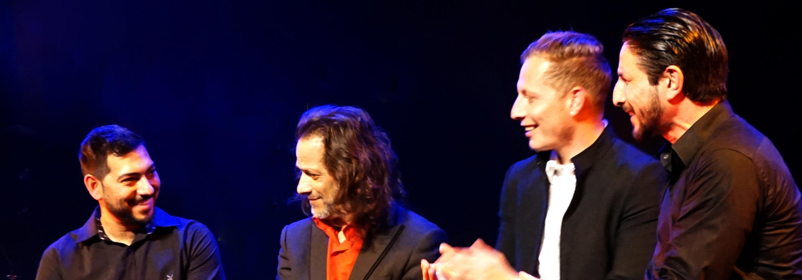 Photo représentant 4 musiciens sur un fond noir, claquant des mains sur des rythmes flamenco