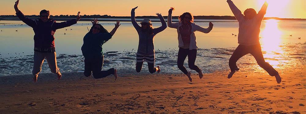 Photo de 5 personnes en train de sauter tous ensemble sur une plage au coucher du soleil