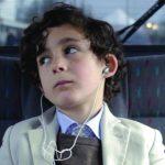Photo représentant un petit garçon dans une voiture qui écoute la musique