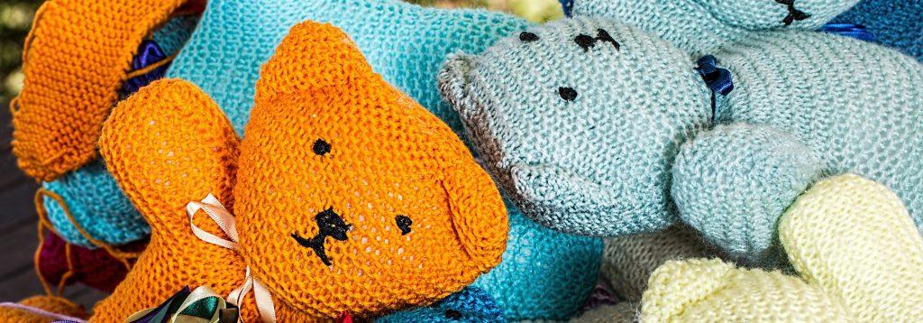 Photo représentant des oursons en peluches tricotés, couleur bleu et orange