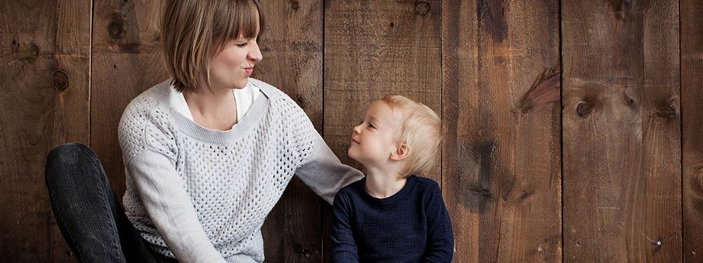 Photo d'une maman assise avec son fils en train de faire des grimaces