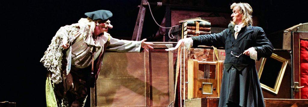 Photo représentant deux personnages sur une scène de théâtre. Un docteur remet une ordonnance à un patient au visage recouvert par un masque de commedia dell'arte
