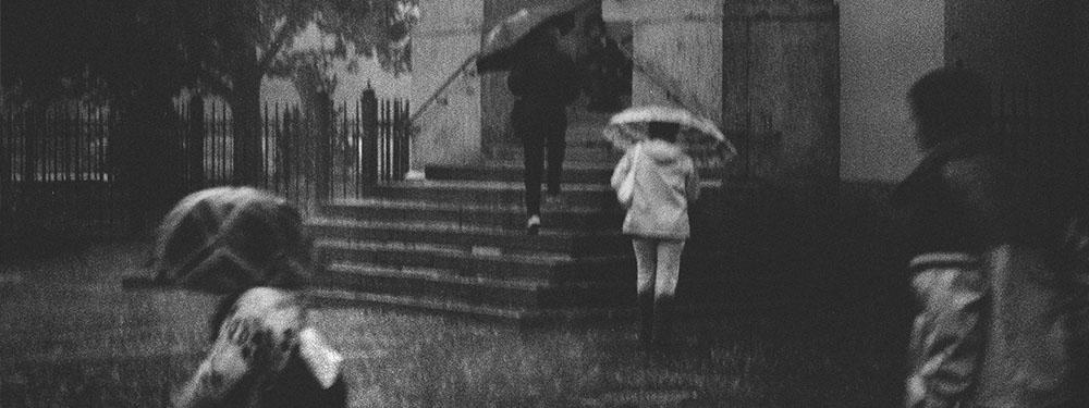 Photo en Noir et blanc de gens marchant sous la pluie parapluie en main
