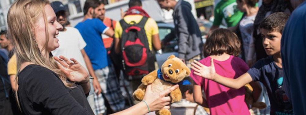 Photo d'une jeune femme donnant une peluche à un enfant réfugié