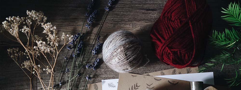 Photos de fleurs séchés , de pelotes de laine, de papeterie posés sur une table