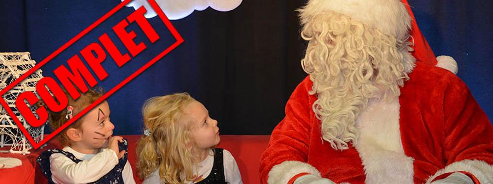 Photo du Père Noël assis sur un canapé rouge avec 2 enfants qui le regardent estampillée d'un logo complet rouge