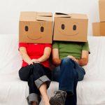 photo d'un couple assis sur un canapé portant des cartons avec des visages dessinés dessus entouré de cartons de déménagement