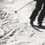 Photo en noir un blanc des jambes d'un skieur en train de dévaler une piste enneigée