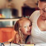 Photo montrant une maman portant son enfants dans les bras et concentré sur un cahier posé sur une table
