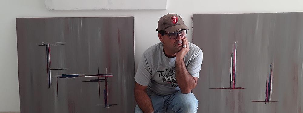 Photo de l'artiste Philippe Aupeix posant accroupi devant ses œuvres
