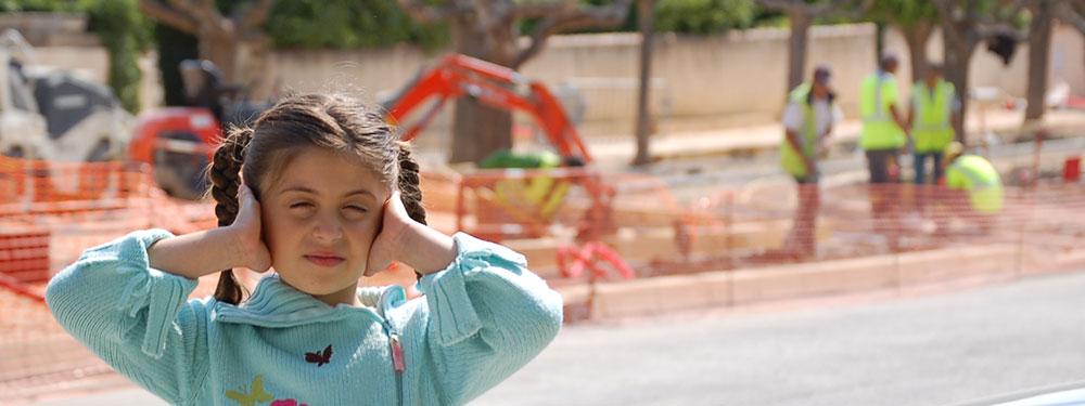 Jeune feille se bouchant les oreilles sur un chantier