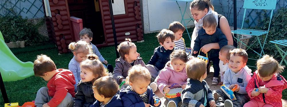Groupe d'enfants prenant le goûter dans la pelouse