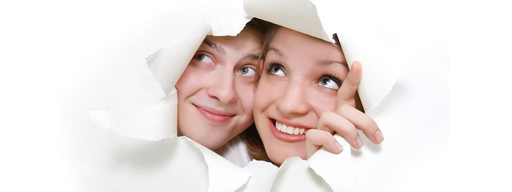 Deux personnes passant la tête à travers une feuille de papier
