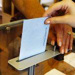 Photo zoomée d'une main au dessus d'une urne de vote tenant une enveloppe de vote prête à être lachée