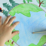 Photo d'un enfant en train de colorier un dessin en forme de terre