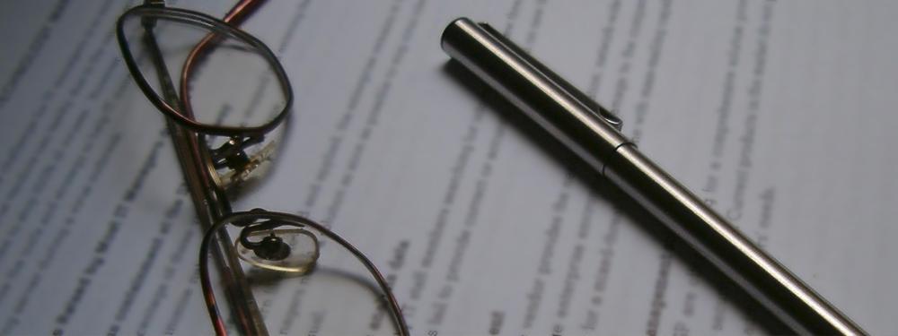 Photo d'un stylo et d'une paire de lunettes posés sur un contrat