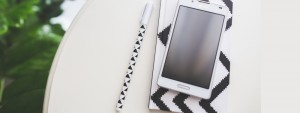 Photo d'un carnet, d'un téléphone et d'un stylo posés sur une table