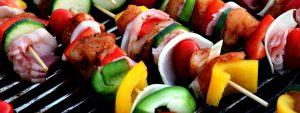 Photo de brochettes de viande en train de cuire sur un barbecue