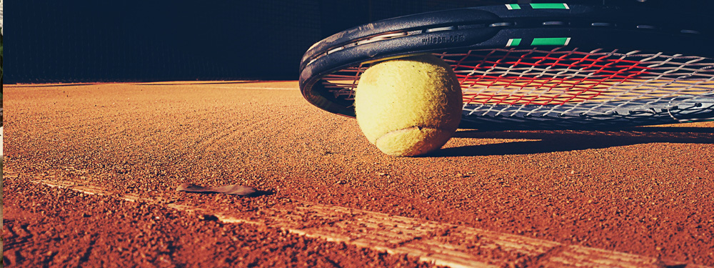 Photo d'une raquette et d'une balle de tennis posés sur un terrain en terre battue