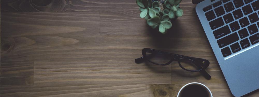 Photo de lunettes posées sur une table à coté d'une tasse de café et d'un ordinateur