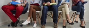 Photo des jambes des personnes assises dans une salle d'attente en attendant de passer un entretien
