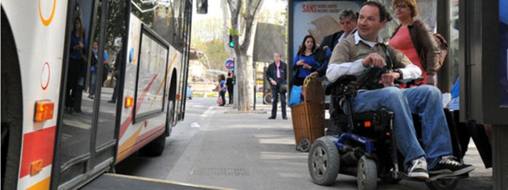 Photo d'une personne à mobilité réduite montant dans un bus accessibus