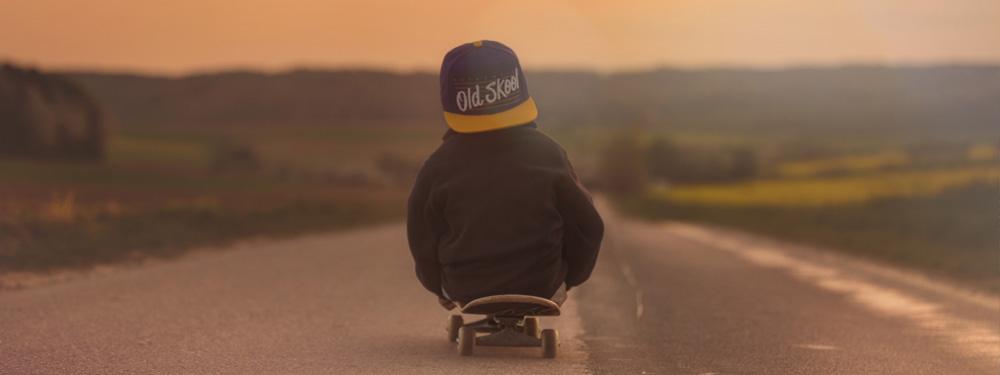 Visuel d'un petit garçon assis sur un skate sur une route deserte