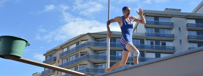 Photo d'un homme qui court sur un toit en combinaison de triathlon