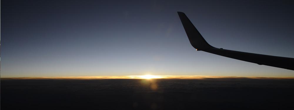 Photo d'une queue d'avion en vol au couché du soleil