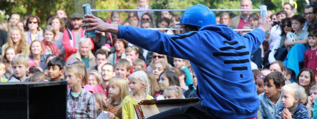 Photo d'un comédien qui sort un filet de ping-pong devant des spectateurs attentifs