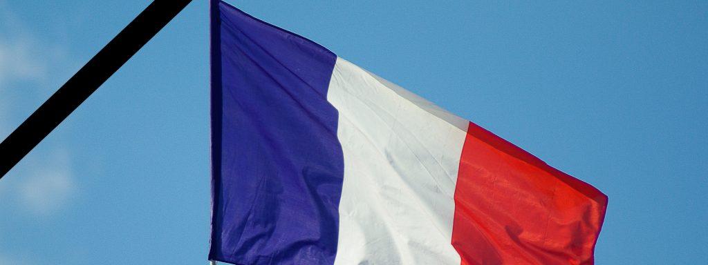 Photo d'un drapeau français barré un bandeau noir représentant le deuil