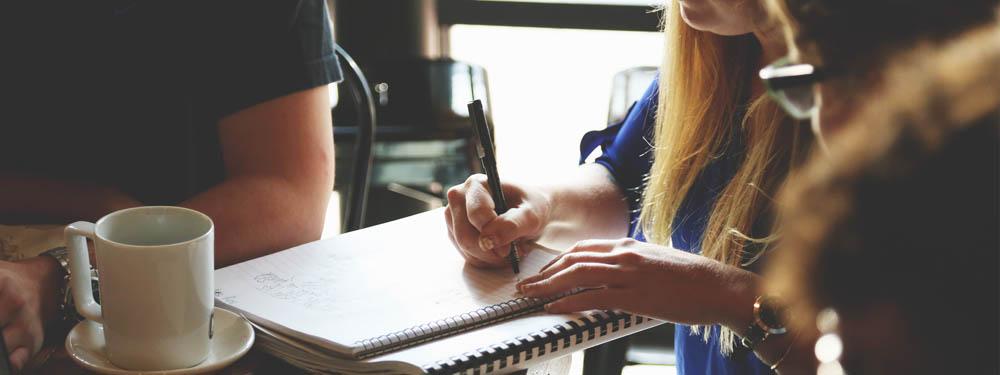 Photo d'une jeune femme blonde en train d'écrire susr un cahier assise devant une tasse de café