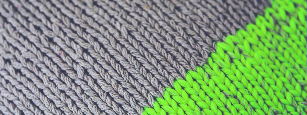 Photo d'une écharpe en laine grise et néon vert vue de près