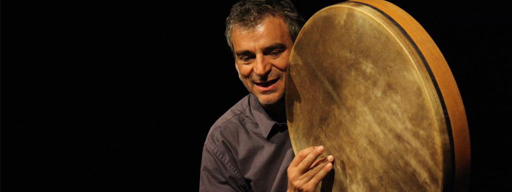 Photo d'un homme sur scène portant dans les mains un instrument de musique (type tambourin géant)