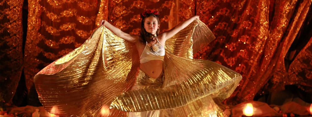 Photo d'une filette en train de danser en tenant 2 voiles de sa robe dans ses mains