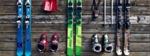 Photo de ski, chaussures, batons de ski, luge posés sur un sol en bois